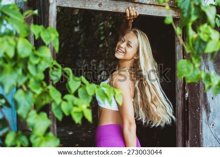 Attractive woman with beautiful long blonde hair and slim body stay in sport wear under the tree, move her hair, look to the camera and smile - stock photo