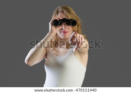 Attractive woman with binoculars and pointing