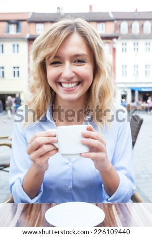 Attractive woman with blond hair drinking a coffee - stock photo