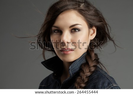 Attractive woman with braided plait in a denim shirt with flying locks - stock photo