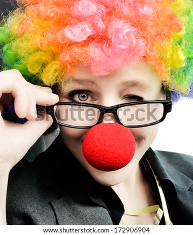 Attractive woman with clown nose and wig winking at the camera - stock photo