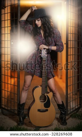 Attractive woman with country look, indoors shot, american country style. Girl  with black cowboy hat and guitar. Beautiful brunette with short dress and boots posing fashion indoors with a guitar - stock photo