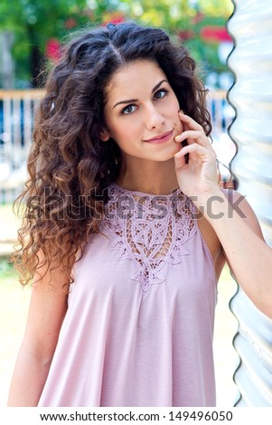 attractive woman with curly hair beauty portrait outside - stock photo