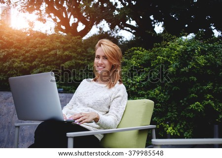 Attractive woman with cute smile sitting with open net-book at modern coffee shop in warm spring day, cheerful female looking at camera during work on laptop computer in comfortable cafe outdoors - stock photo
