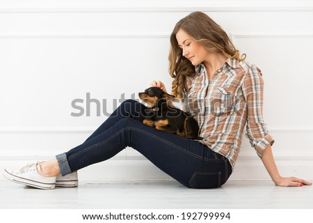 Attractive woman with dog on the floor - stock photo
