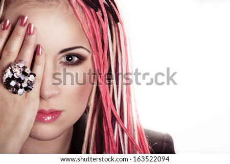 Attractive woman with freaky pink dreadlocks is closing her right eye with  hand in a giant ring - stock photo