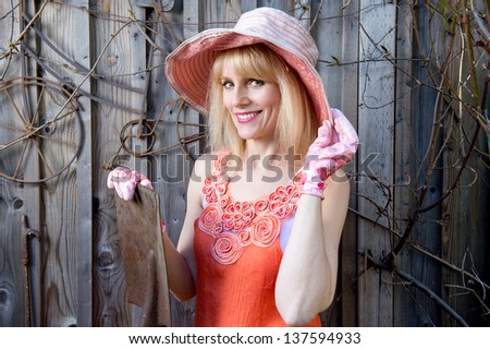 Attractive woman with gardening hat and gloves poses in front of old fence