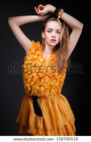 Attractive woman with hands above her head, beauty make-up, pretty long hair and yellow dress with dark belt, looking at camera