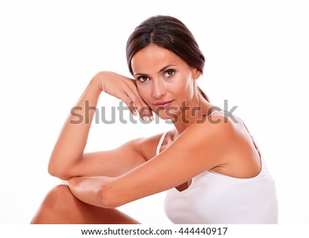 Attractive woman with her knee up and her hand to face while looking at camera and wearing a white tank top, hair tied back isolated