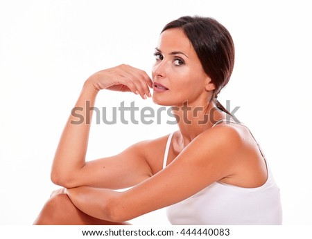 Attractive woman with her knee up and her hand to face while looking at camera thoughtfully wearing a white tank top, hair tied back isolated