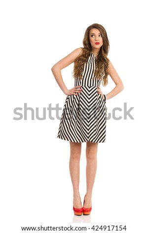 Attractive woman with long brown hair wearing black and white striped dress and high heels posing with hands on hip and looking at camera, Full length studio shot isolated on white. - stock photo