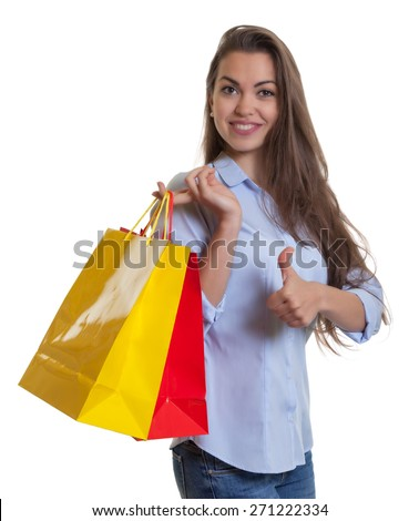 Attractive woman with long dark hair and shopping bags showing thumb - stock photo