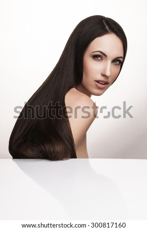 attractive woman with long straight brown hair looking at camera, on white studio background. Beautiful Woman with Long Healthy and Shiny Smooth Brown Hair. Hairstyle, haircare concept. - stock photo