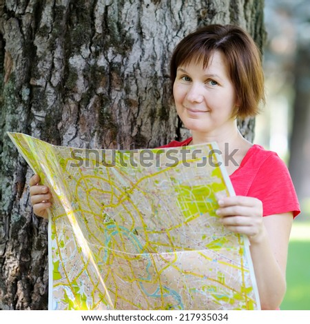 Attractive woman with map under a tree