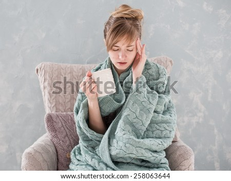 Attractive woman with natural blond hair posing without makeup with headache and white cup of hot drink wrapped with blanket at home - stock photo