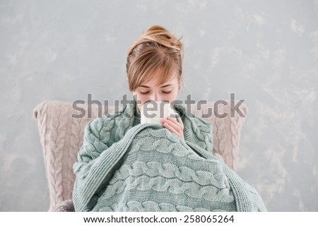 Attractive woman with natural blond hair posing without makeup with white cup of hot drink wrapped with blanket at home - stock photo