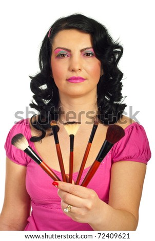 Attractive woman with pink creative make up giving brushes set isolated on white background