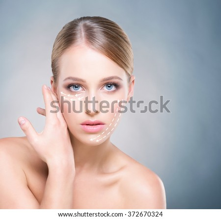 Attractive woman with pure skin and beautiful, blue eyes over navy background. Plastic surgery concept. - stock photo
