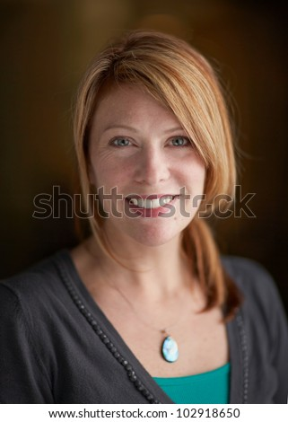 Attractive woman with red hair smiling happy headshot, focus on face - stock photo