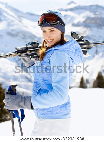 Attractive woman with ski at the mountains - stock photo