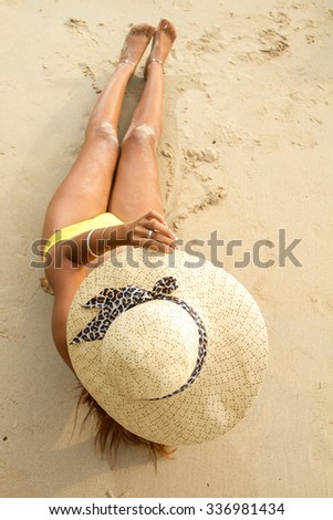 Attractive woman with straw hat on the beach - stock photo