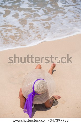 Attractive woman with straw hat on the beach