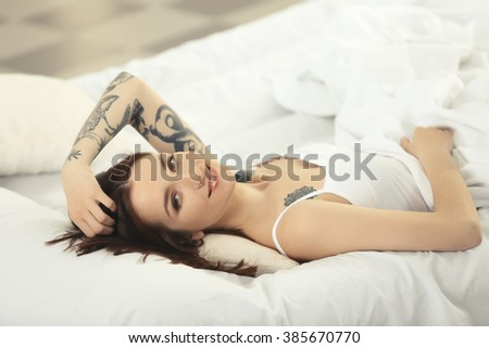 Attractive woman with tattoo lying on the bed
