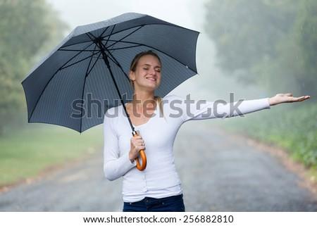 attractive woman with umbrella enjoying the rain - stock photo