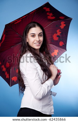 Attractive woman with umbrella on blue background
