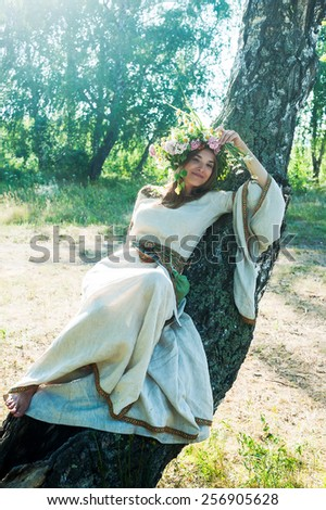 Attractive Woman with Wreath of Flowers lays down on birch (Ivan Kupala Holiday Celebration) - stock photo