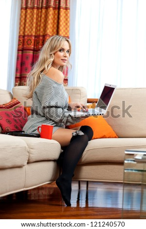 attractive woman working on her laptop in her living room sofa