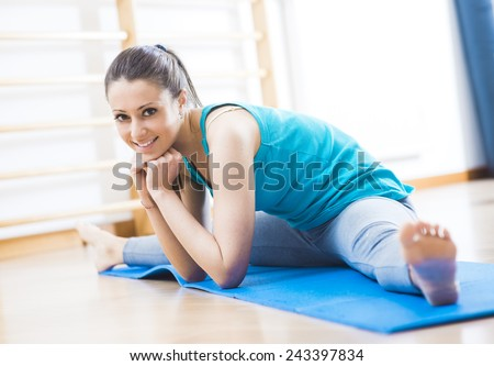 Attractive woman working out at gym doing stretching exercises on a mat for legs. - stock photo