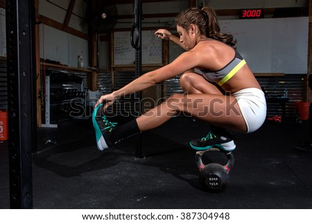 Attractive woman working out in a gym doing a pistol on a kettle bell - stock photo