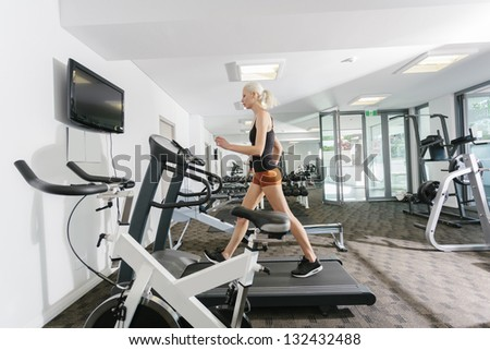 Attractive woman working out in gym - stock photo