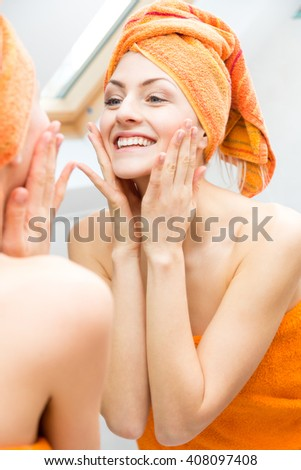 Attractive woman wrapped in towel touching the sides of her face with big happy smile in reflection on mirror - stock photo