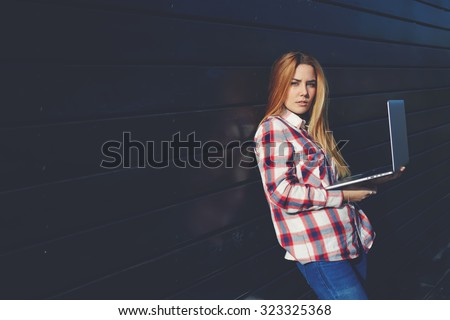 Attractive women holding laptop computer while standing near wall background with copy space for your information or advertising, young female freelancer using net-book for remote job during free time - stock photo