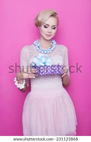 Attractive women holding purple gift box with ribbon. Studio portrait over purple background - stock photo