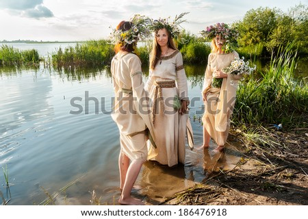 Attractive Women with Wreath of Flowers standing on lake bank (Ivan Kupala Holiday Celebration) - stock photo