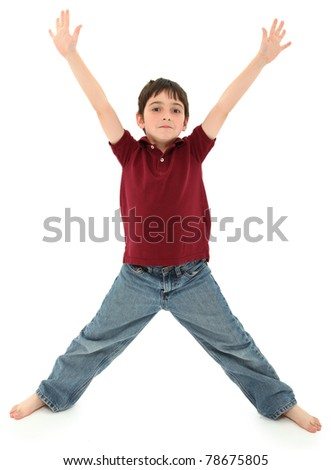 Attractive 8 year old french american boy standing in the shape of a letter x or ready to hug.  Standing over white background. - stock photo