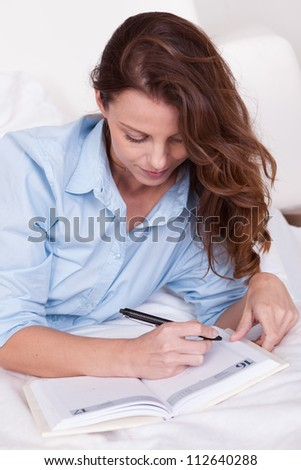 Attractive you woman lying relaxing on a sleeper couch writing in her diary