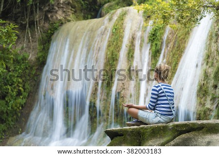 Attractive youn woman during meditation near the waterfall, Java, Indonesia