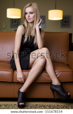 attractive young adult  blonde woman in black dress sitting on brown couch in luxury apartment - stock photo