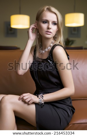 attractive young adult blonde woman in black dress sitting on the brown couch - stock photo