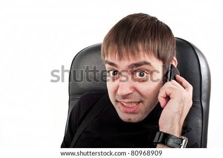 attractive young adult businessman Caucasian Europeans sitting in a leather  with telephone, cell phone and emotionally speaking, and looks into the camera isolated over white, isolated, talking - stock photo