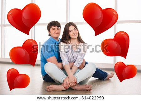 Attractive young adult couple sitting close on floor in home smiling and laughing. - stock photo