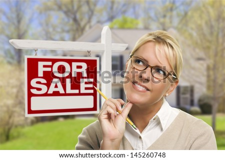 Attractive Young Adult Woman with Pencil in Front of For Sale Real Estate Sign and House. - stock photo