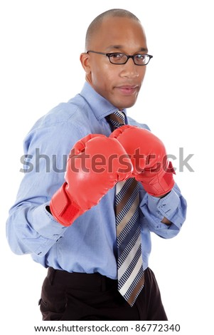 Attractive young African American businessman wearing boxing gloves. Blow with right arm. Studio shot. White background. - stock photo