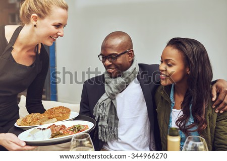 Attractive young African American couple sitting arm in arm at a restaurant table being served dinner by a smiling young Caucasian waitress - stock photo
