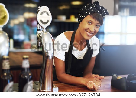 Attractive young African American small business owner dressed in a head scarf and apron leaning on the counter of her pub smiling happily at the camera with a confident smile - stock photo