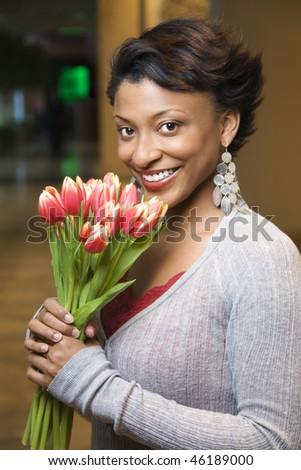 Attractive young African-American woman smiles for the camera. She is holding a bouquet of tulips. Vertical shot. - stock photo